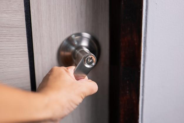 A pessoa abre uma porta entre os quartos. porta aberta no apartamento