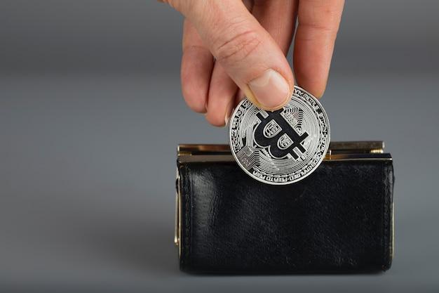 A pessoa coloca o bitcoin em uma carteira preta. fechar-se