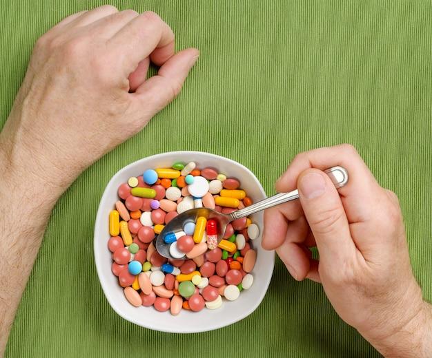 A pessoa come muitos comprimidos, comprimidos, cápsulas de uma tigela com uma colher na mesa de jantar