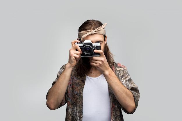A pessoa criativa do jovem hippie hipster fotografa em uma câmera de filme antigo, o artista criador em um fundo branco studio parece através de uma lente