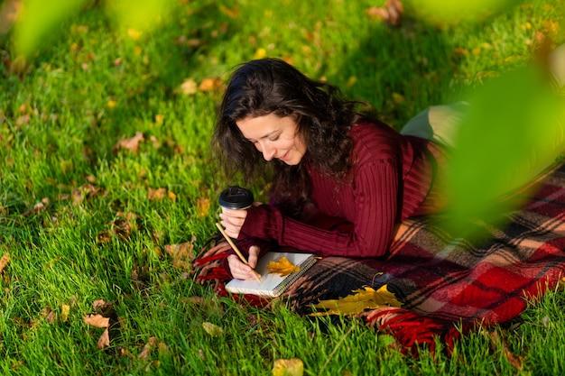 A pessoa escreve notas deitada no gramado no parque de outono