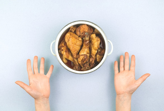 A pessoa está insatisfeita com a quantidade de comida, a pessoa conceitual quer mais comida, frango frito na panela, foto da vista superior