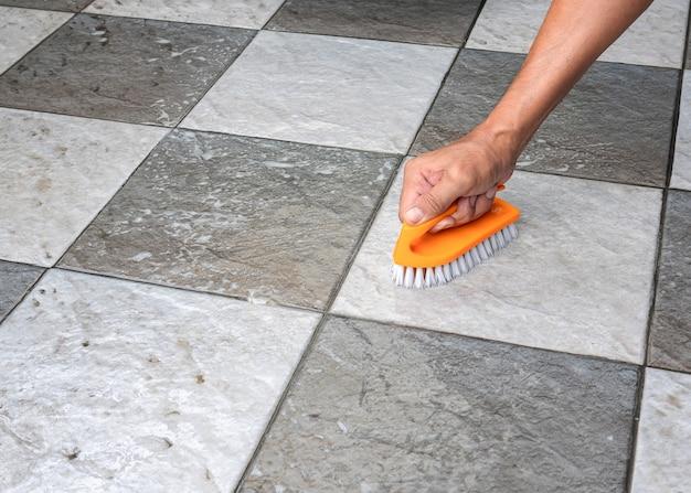 A pessoa está limpando o piso de cerâmica