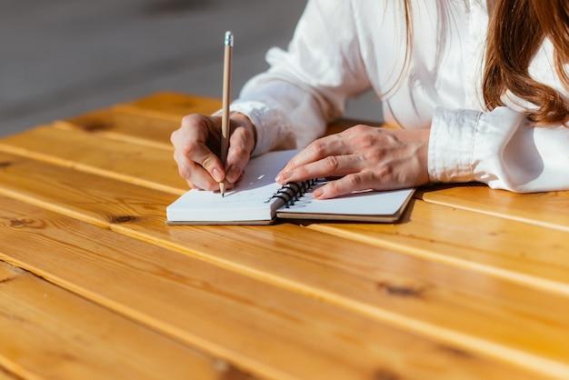 A pessoa faz anotações com um lápis em um caderno enquanto está sentada em um café no verão na rua