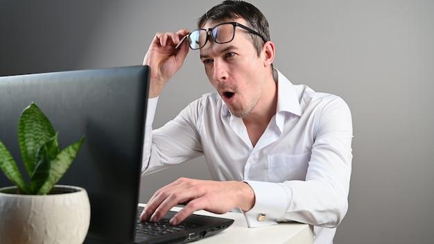 A pessoa ficou muito surpresa sentada em frente ao computador