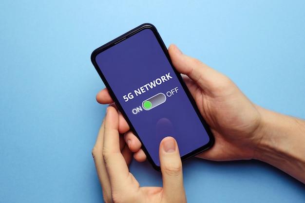 A pessoa na tela do smartphone liga a rede 5g.