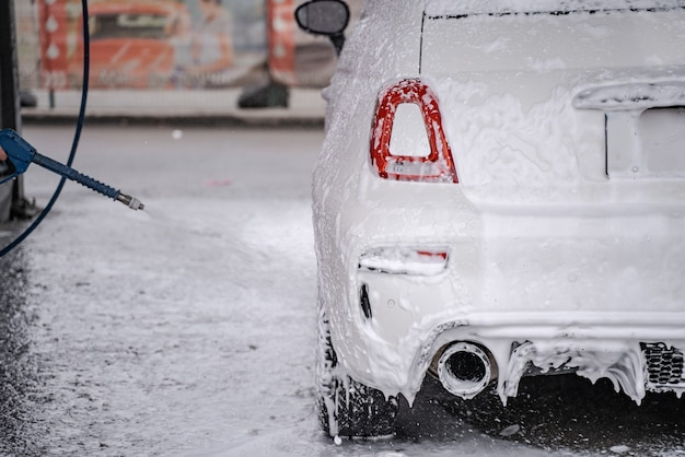 A pessoa por trás da cena lava um automóvel pessoal na lavagem automática de carros com mangueira. auto coberto com água e sabão