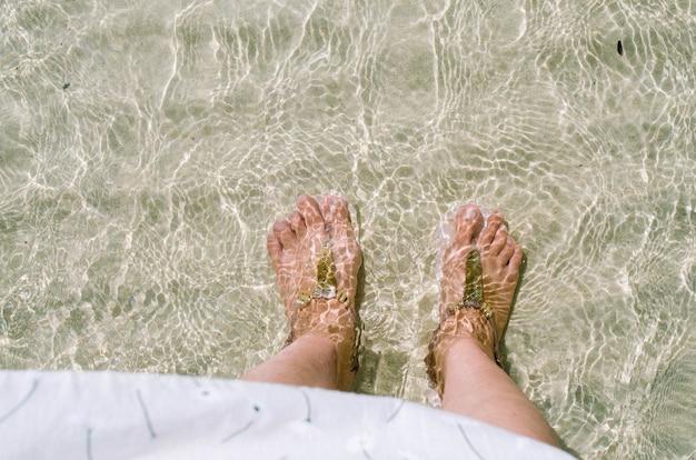 A pessoa que está no mar do oceano acena no sandy beach.