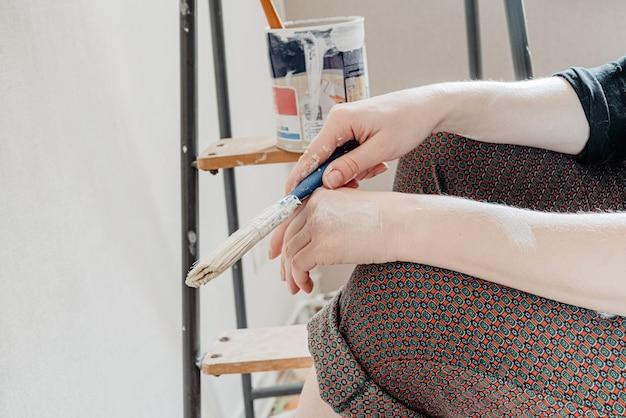 A pessoa se senta perto de uma escada, segurando o pincel na mão e descansando depois de pintar as paredes