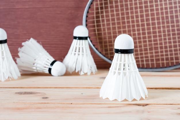 A peteca de badminton e raquete na natureza fundo de madeira