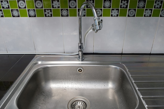 A pia de metal limpa com torneira cromada após a lavagem no balcão moderno, dentro da cozinha da casa urbana, vista frontal para o espaço da cópia.