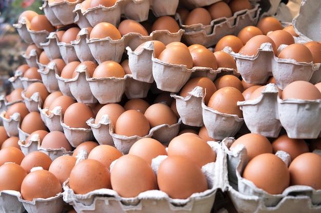 A pilha da galinha fresca e crua orgânica da galinha eggs para a venda na exploração agrícola da agricultura do mercado da bandeja.