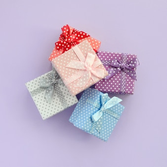 A pilha de caixas de presente coloridas pequenas com fitas encontra-se em um fundo violeta.