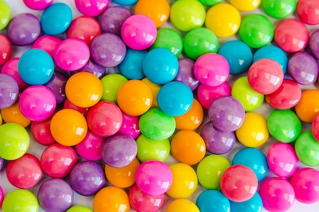 A pilha de chocolates doces coloridos dos doces revestiu no livro branco. fundo colorido coleção