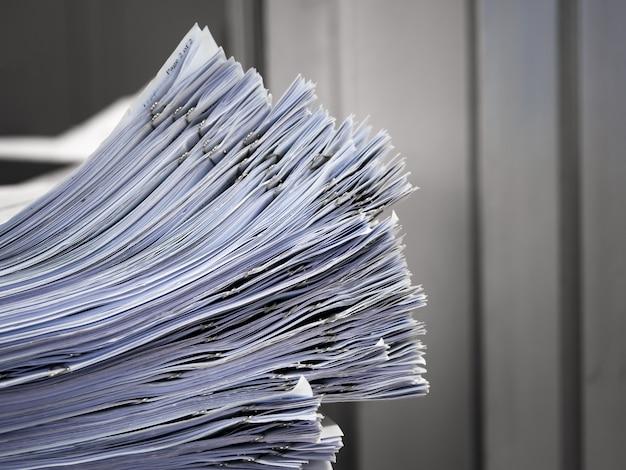A pilha de documentos colocados na mesa.