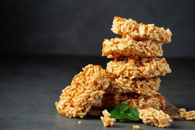 A pilha de lanche tailandês kao tan ou biscoito de arroz no chão escuro