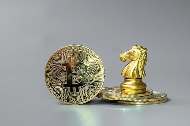 A pilha de moedas de criptomoeda golden bitcoin e a peça do chess knight, crypto is digital money dentro da rede blockchain, são trocadas usando tecnologia e troca de internet online. conceito financeiro