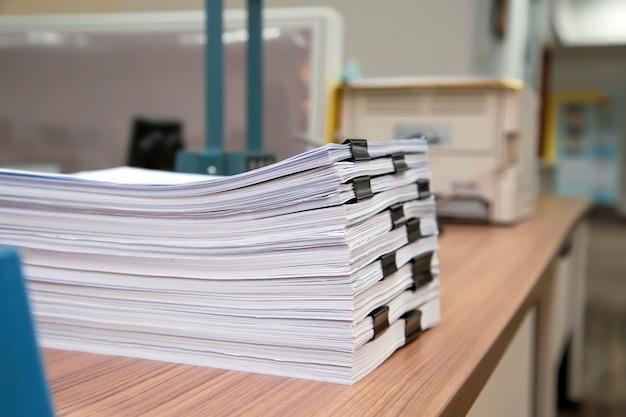 A pilha de muitos documentos da papelada no escritório da mesa empilha acima.
