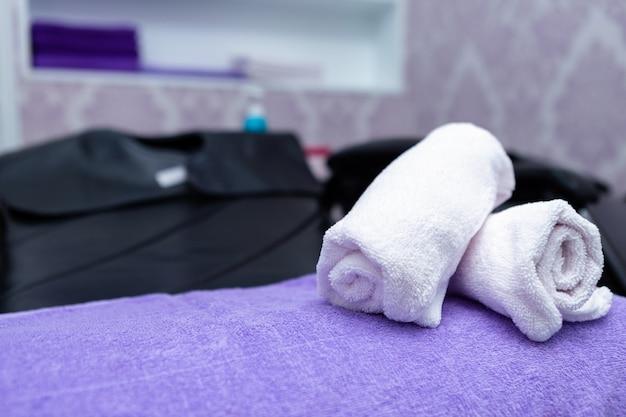A pilha de toalhas dos termas de turquesa em poltronas com lavagem está no salão de beleza do cabeleireiro.