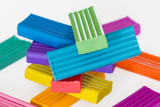A pilha do plasticine colorido cola no fundo claro. foco seletivo