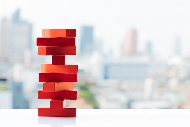 A pilha vermelha da torre dos blocos de madeira brinca com fundos da cidade e do céu.