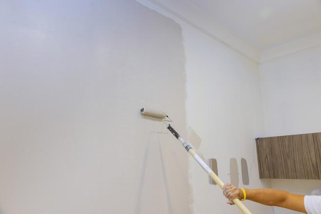 A pintura a rolo com pincel fecha detalhes de paredes pintadas, trabalhador industrial usando rolo