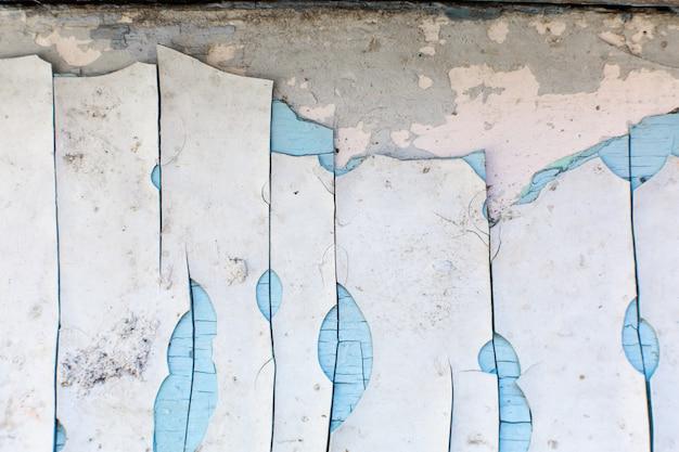 A pintura descasca fora da parede. moinho de pintura com um grande número de camadas de tinta velha