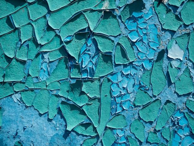 A pintura descascada velha é azul na parede. close-up, fundo, textura