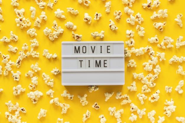 A pipoca e o lightbox dispersados text o tempo de filme no fundo de papel amarelo.