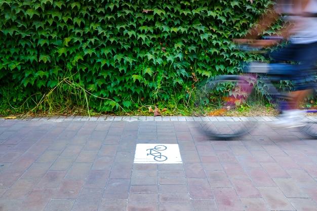 A pista da bicicleta separou do tráfego com o sinal, motociclista borrado.