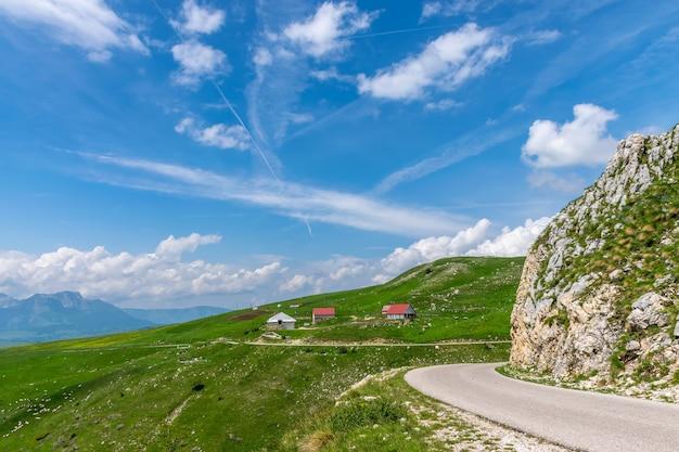 A pitoresca vila está entre os prados nas altas montanhas.