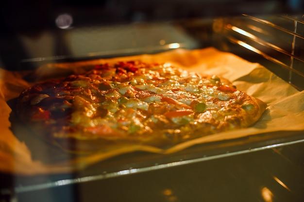 A pizza caseiro é cozida no forno em uma folha de cozimento e em um papel de pergaminho. a vista através do vidro.