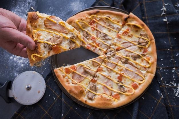 A pizza italiana tradicional com chiken na obscuridade - mesa da pedra azul. homem corta pizza com uma faca