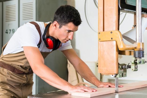 A placa de estaca do carpinteiro com gabarito viu em sua bancada de trabalho