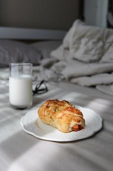 A placa do rolo de salsicha com leite está em cima da cama. café da manhã no conceito de cama.