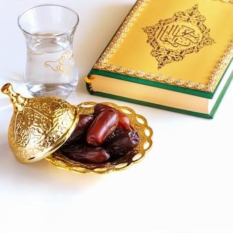 A placa dourada árabe das datas secadas orgânicas, a água do copo e o livro do quran.