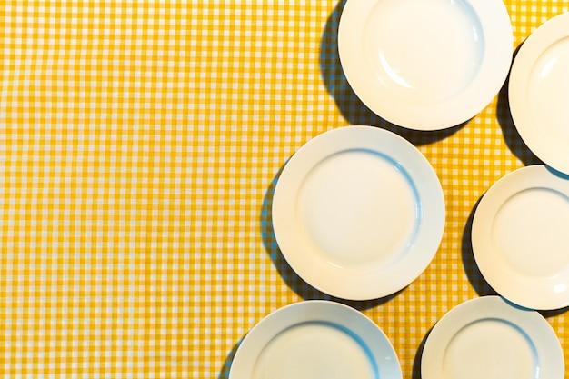 A placa na toalha de mesa quadriculada amarela