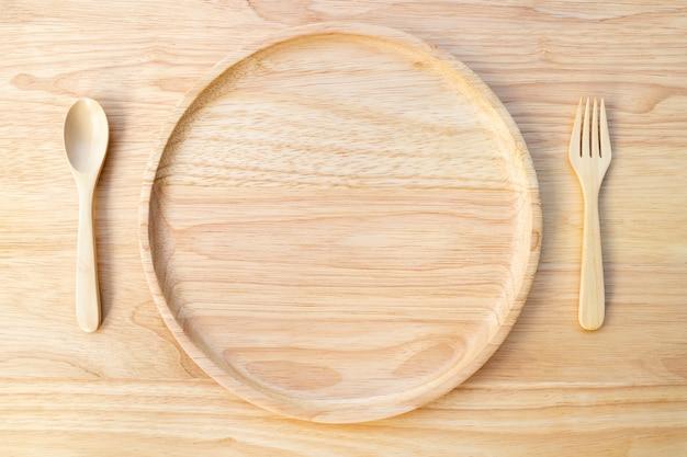 A placa redonda de madeira de borracha natural, lacada em cima de uma tábua de madeira, com uma colher e um garfo.