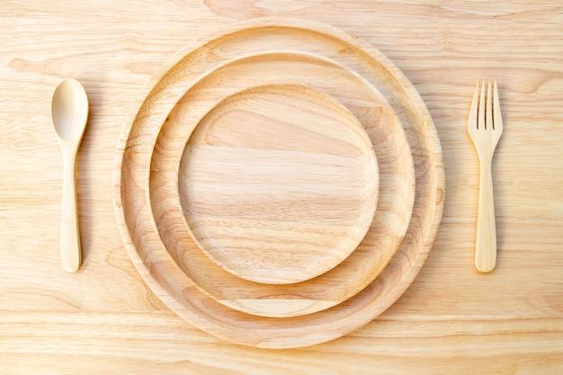 A placa redonda de madeira natural de borracha, lacada, é empilhada sobre uma tábua de madeira, com uma colher e um garfo.