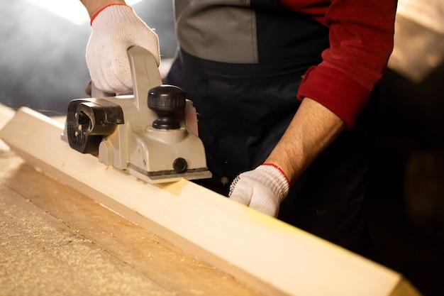 A plaina elétrica chanfra a peça de madeira na bancada