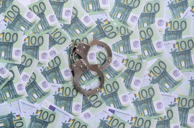 A polícia algema-se em um conjunto de denominações monetárias verdes de 100 euros. um monte de dinheiro forma uma pilha infinita