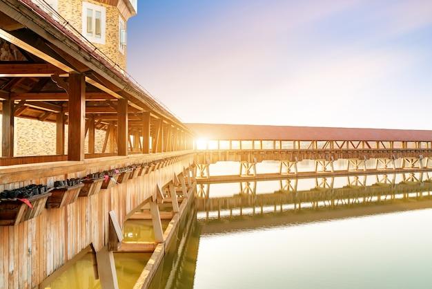 A ponte coberta de estilo europeu está situada junto ao rio, a paisagem urbana de nanchang, na china.