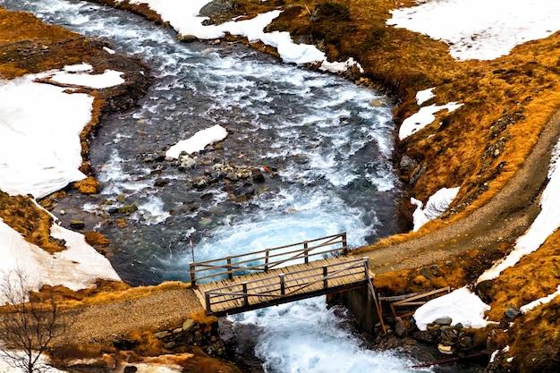 A ponte de madeira de fluxo rápido do rio