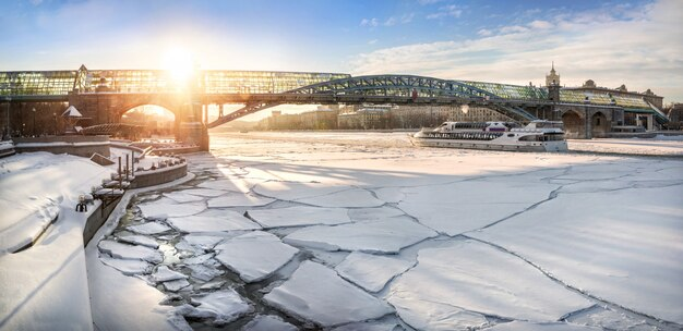 A ponte de pedestres andreevsky sobre o rio congelado de moscou e um barco