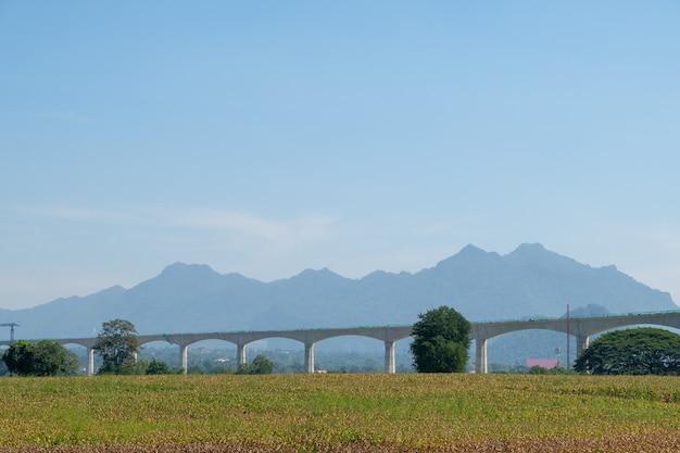 A ponte ferroviária elevada do projeto de via dupla está em construção para passar da fazenda de milho até a pequena cidade no vale perto da cordilheira, vista frontal com o espaço da cópia.