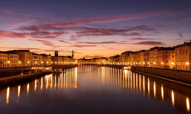 A ponte ponte di mezzo sobre o rio arno ao pôr do sol dourado à noite. pisa, região da toscana, itália