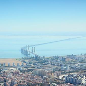 A ponte vasco da gama é uma ponte estaiada flanqueada por viadutos e varandas em lisboa, capital de portugal