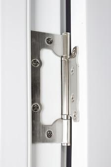 A porta de aço inoxidável tem dobradiças em uma porta branca. dobradiças na porta branca.