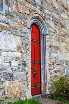 A porta vermelha para a igreja de pedra medieval