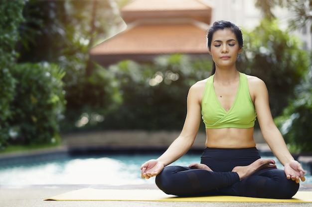 A pose praticando da ioga da mulher medita na posição de lótus que senta-se perto da piscina.